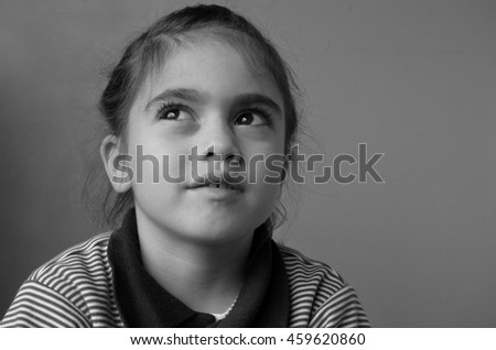 Young girl (age 6) thinks about her future. Childhood concept. real people copy space (BW) - stock photo