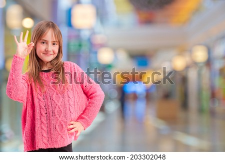 young girl all right gesture in a shopping center - stock photo