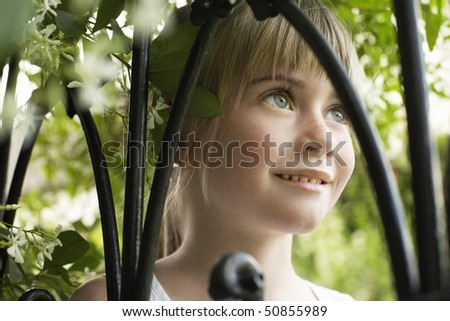 Young girl among branches, smiling, portrait, close-up - stock photo