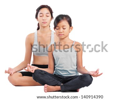 Young girl and a lady in yoga meditation position. - stock photo