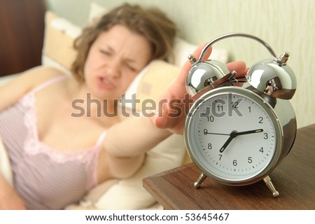 Young girl and alarm clock. Bedtime scene