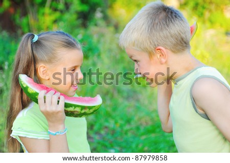 Young girl and boy eating watermelon in the park