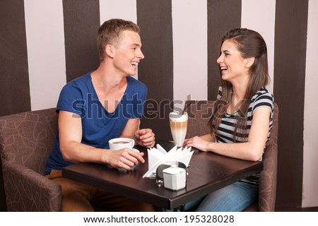 young girl and boy laughing in cafe. beautiful man and woman drinking coffee - stock photo