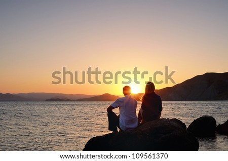 Young girl and boy sitting on a rock by the sea and watching the sunset - stock photo