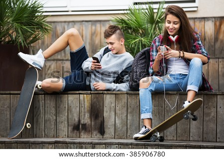 Young girl and boy teens playing on mobile phones and listening to music outdoors - stock photo