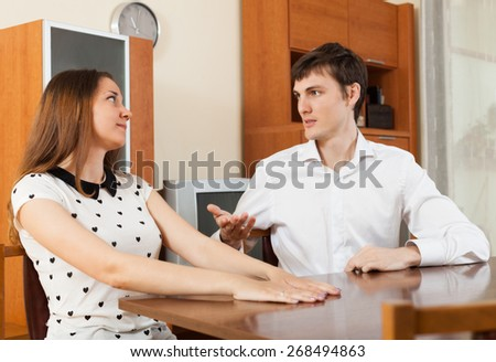 Young girl and guy  talking  in living room at home