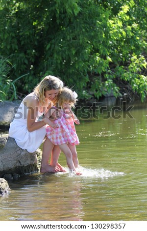 young girl and her little daughter squirting water at the lake