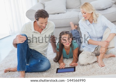 Young girl and her parents using a tablet lying on a carpet - stock photo