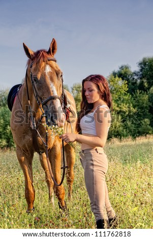 Young girl and horse on a summer meadow on a sunset