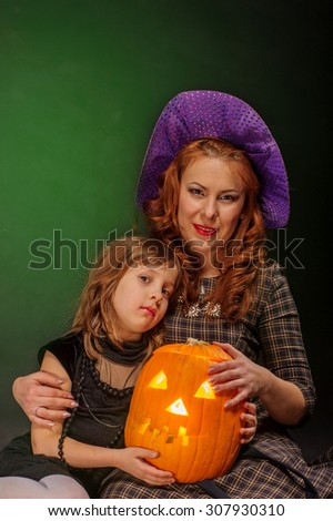 Young girl and mature mother at Halloween party reading magic book