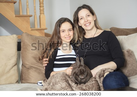 Young girl and mother with his pet rabbit at home.