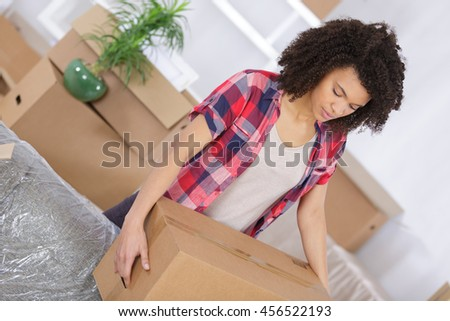 young girl arranging interior and unpacking at new apartment