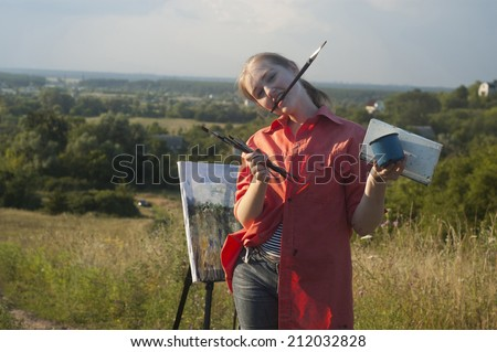 Young girl-artist is painting with watercolor on the plein Air. Rural landscape is on the background. - stock photo
