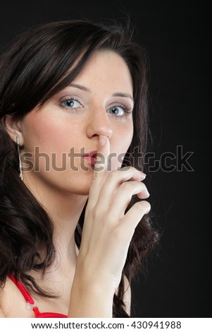 Young girl asking for silence beautiful woman with finger on her lips - copyspace - stock photo