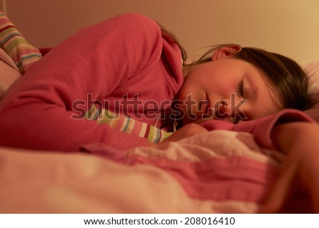 Young Girl Asleep In Bed At Night