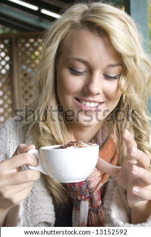 young girl at a cafe drinking coffee - stock photo