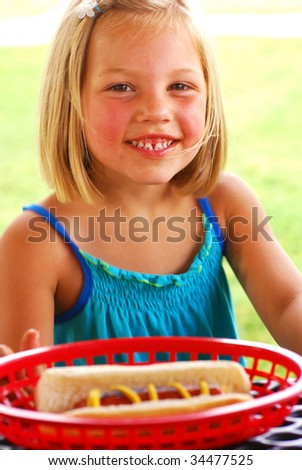 Young girl at a picnic table with hot dog