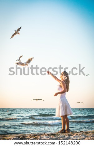 Young Girl at Beach are Feeding Seagulls - stock photo