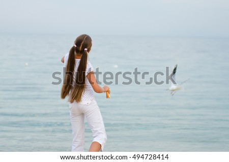 Young Girl at Beach are Feeding Seagulls. adorable little girl feeding birds in the sea, playing with the seagulls. girl with long hair feeding seagulls on the shore. motion blur