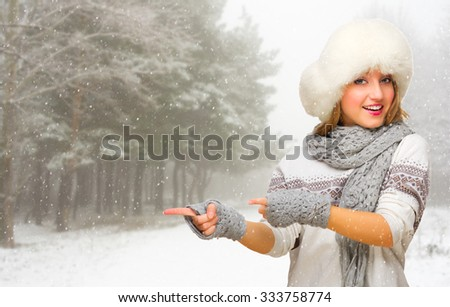Young girl at snowy winter forest shows pointing gesture - stock photo