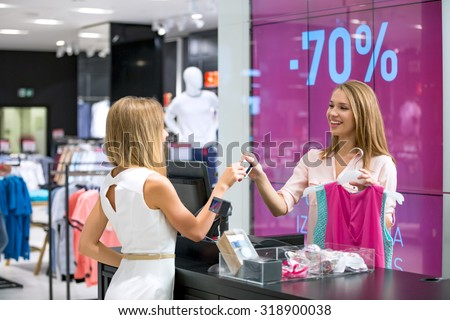 Young girl at the checkout makes shopping - stock photo