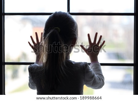 Young girl at window (in partial silhouette) hands pressed against window, pensive or wanting out?  - stock photo