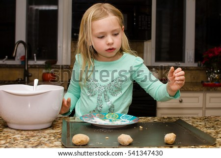 young girl baking cookies in kitchen
