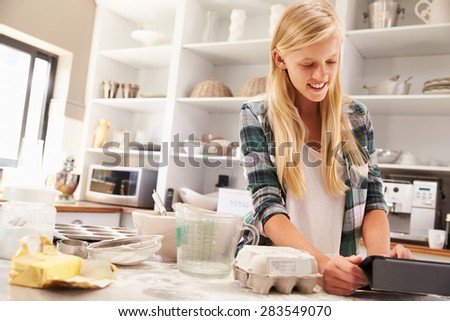 Young girl baking following recipe on a tablet - stock photo
