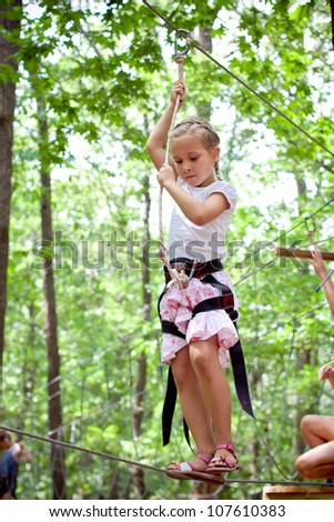 Young girl balancing on rope in adventure climbing high wire park