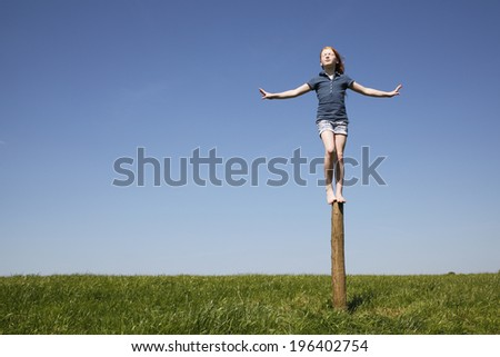 Young girl balancing outdoors on a trunk of a tree - stock photo