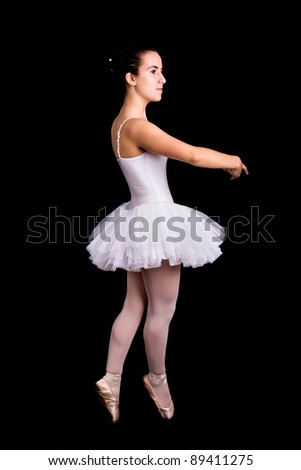 Young girl ballet dancer standing against black background - stock photo