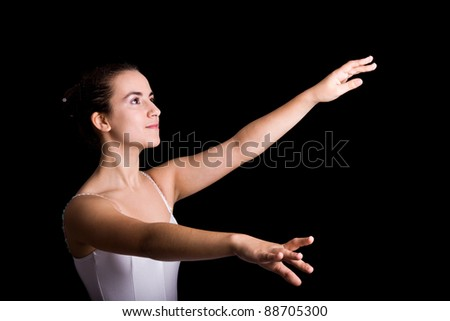Young girl ballet dancer standing in a tutu on a black background - stock photo