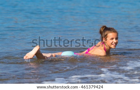 Young girl bathing in the sea, beach