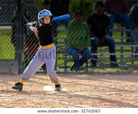 Young Girl Batting at Youth Baseball Game - stock photo