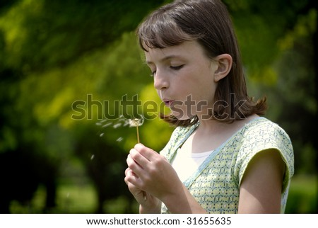 Young girl blowing a dandilion with blue sky