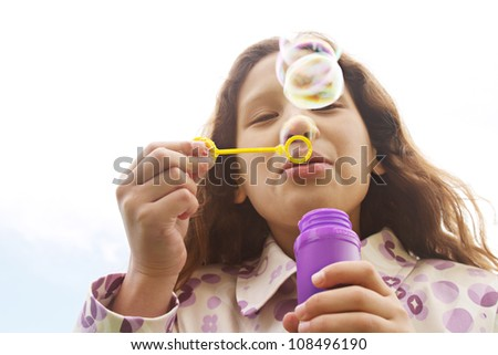Young girl blowing bubbles against the sky, smiling. - stock photo