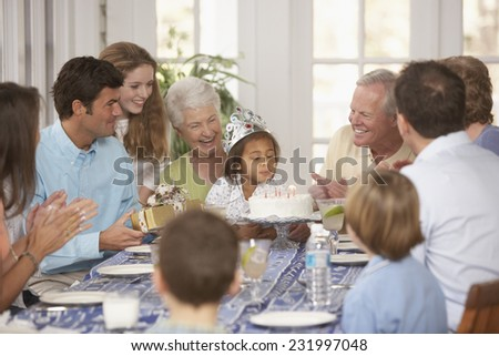 Young Girl Blowing Out Birthday Candles - stock photo