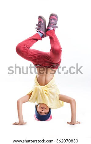 Young girl break dancer performing headstand against white - stock photo