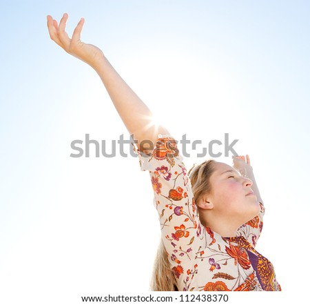 Young girl breathing fresh air with her arms raised against a blue sky, with the sun rays filtering through her arm. - stock photo