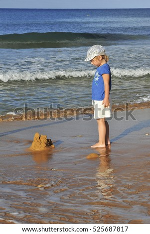 Young girl builds a sand castle on the beach, Gozo, Malta