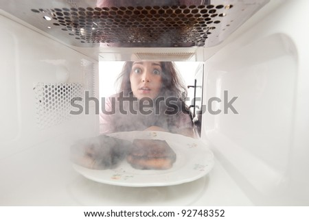Young girl burn toasts in a microwave - stock photo