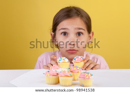 Young girl caught stealing two cupcakes with a guilty expression on a yellow background - stock photo