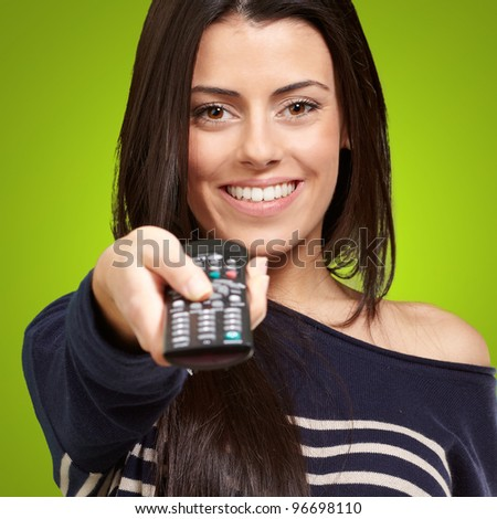 young girl changing channel over green background - stock photo