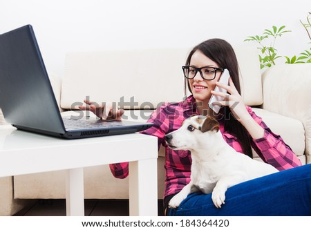 Young girl chatting on mobile phone, using computer  with pet dog in lap - stock photo
