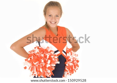 Young girl cheerleader standing with orange pompoms - stock photo