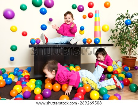 Young girl child having fun playing with colorful plastic balls - stock photo