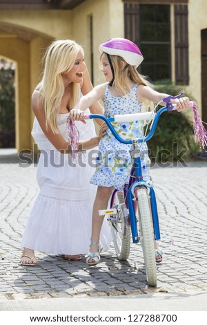 Young girl child riding a bicycle with her happy excited mother parent giving encouragement alongside her - stock photo