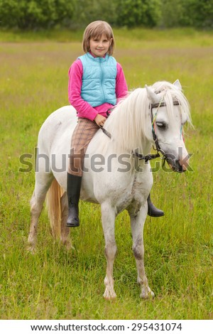 Young girl child sitting astride a white horse and smiling - stock photo