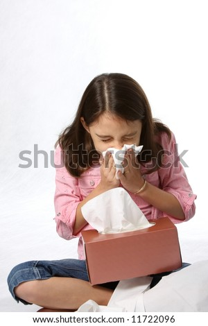 young girl / child with cold blowing her nose with tissues