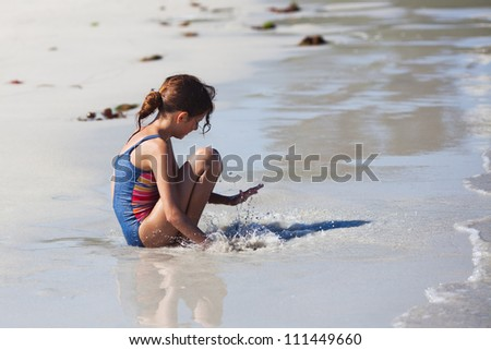young girl claps her hand in the water - stock photo
